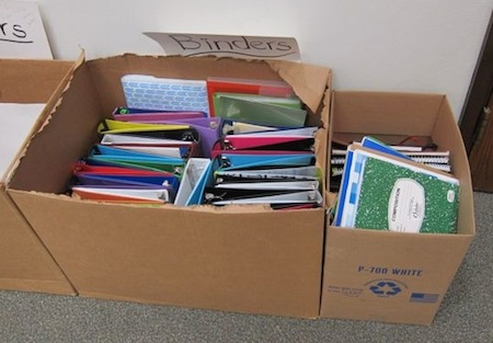 Two large cardboard boxes filled with barely used school binders and notebooks