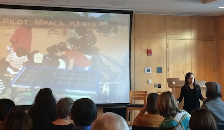 Crowd viewing large screen with picture from Kenya of solar panel research.