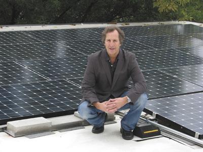 2011 award winner Charlie Yedlin in front of solar panel display