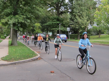 Bicyclists riding single file along a suburban street
