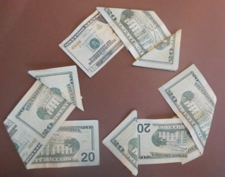 $20 bills folded into arrows creating a triangular recycling symbol on brown background
