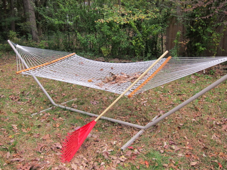 A red rake propped in front of a white hammock on lawn area