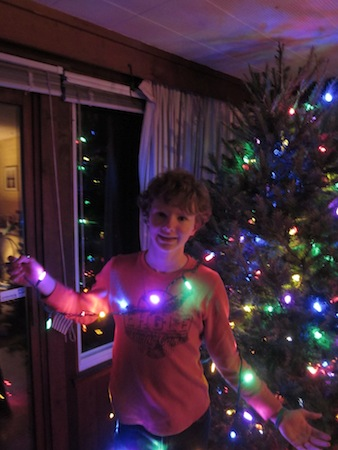 boy holding string of lights in front of Christmas tree