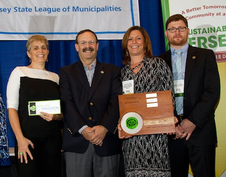 four people, one holding plaque, at awards ceremony