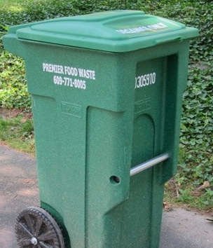 Close up of green rolling food waste bin at side of driveway
