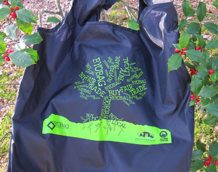 Black fabric bag with green tree image hanging on holly tree