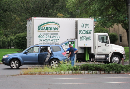 Car unloading documents in front of shredding truck