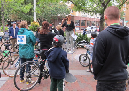 Speaker addressing adults with bicycles and youth with skateboard.
