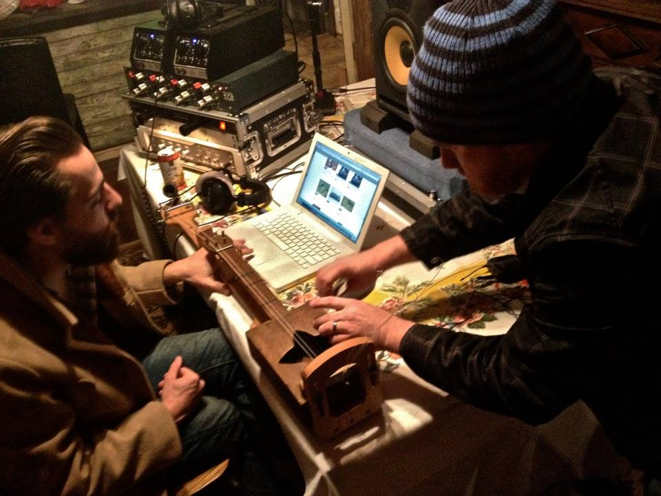 Engineers Curry Weber (right) and Matt Ross-Spang (left) delicately attach a microphone to a turn of the century  cigar box guitar for the field recording session at the Shack Up Inn. Photo by Nikki Johnson.