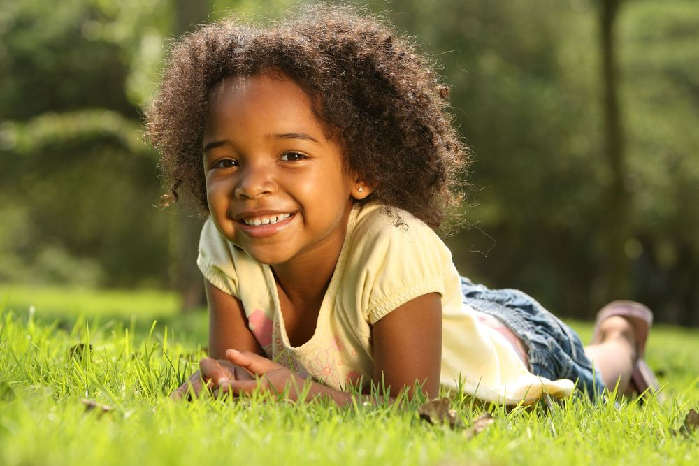 Young girl laying on grass