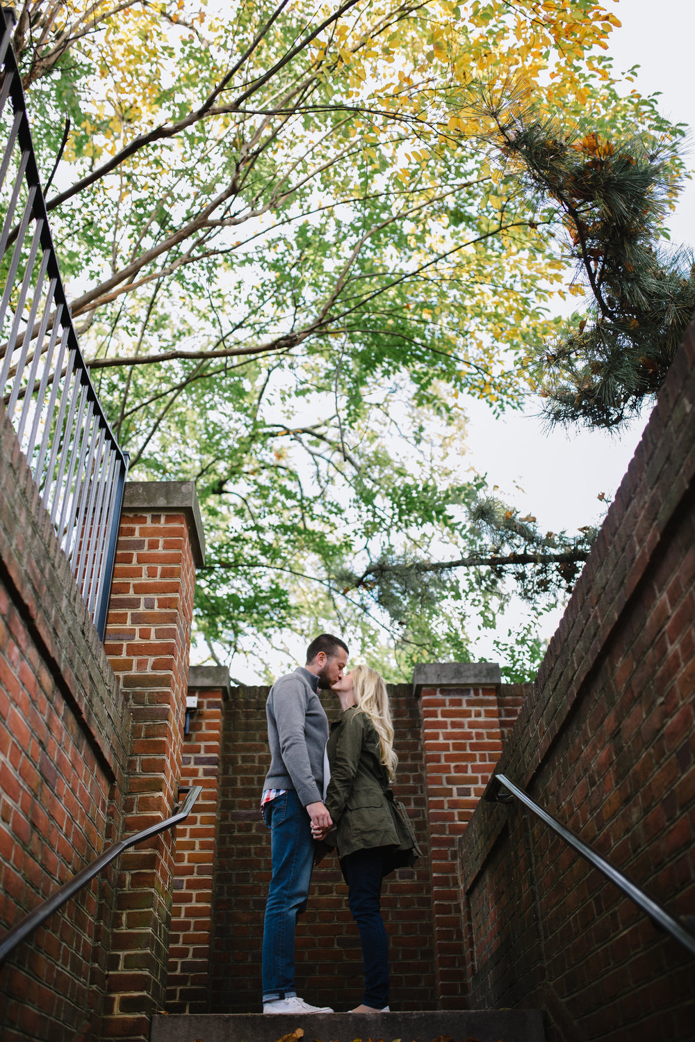 sharing a kiss at dumbarton oaks for engagement photos