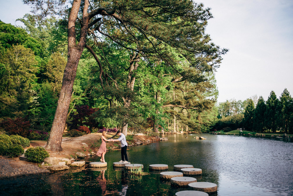 engaged couple in park crossing stepping stones over pond