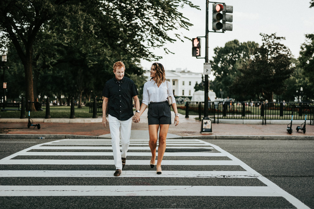 couple holding hands on crosswalk in front of the White House in Washington D.C.