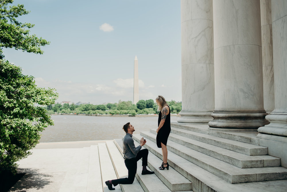 Man proposing on steps of Thomas Jefferson Memorial with the Tidal Basin and Washington Monument in background