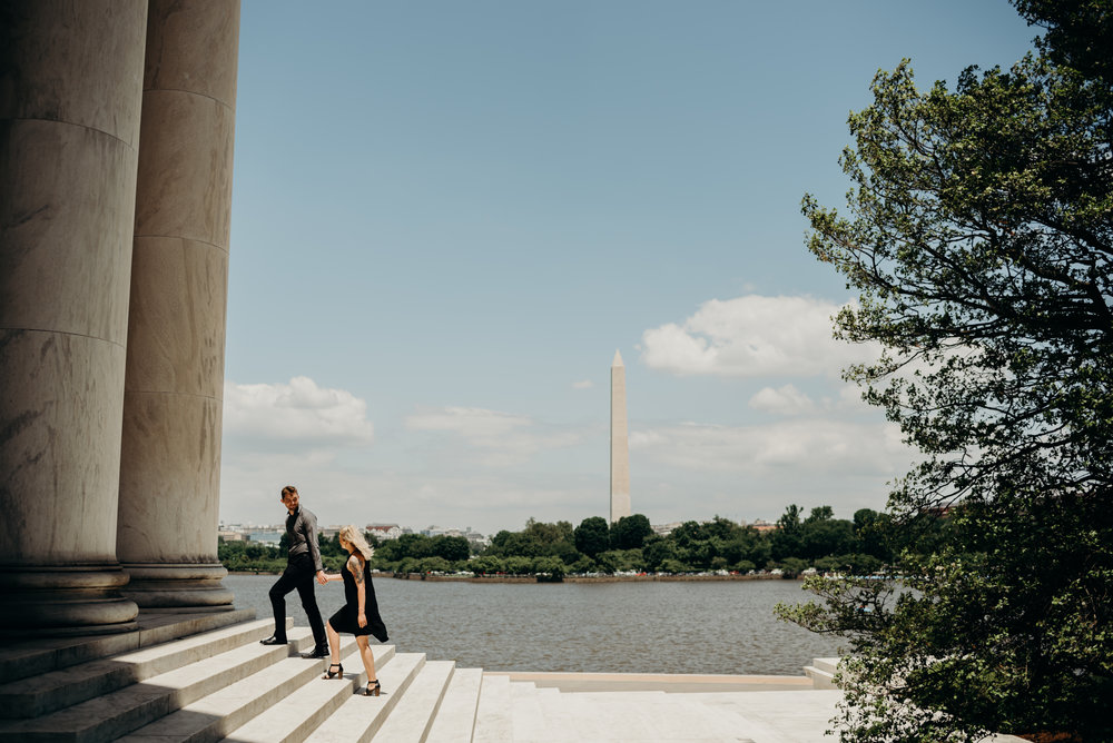 engaged couple climbing steps of Thomas Jefferson Memorial with Tidal Basin and Washington Monument in background