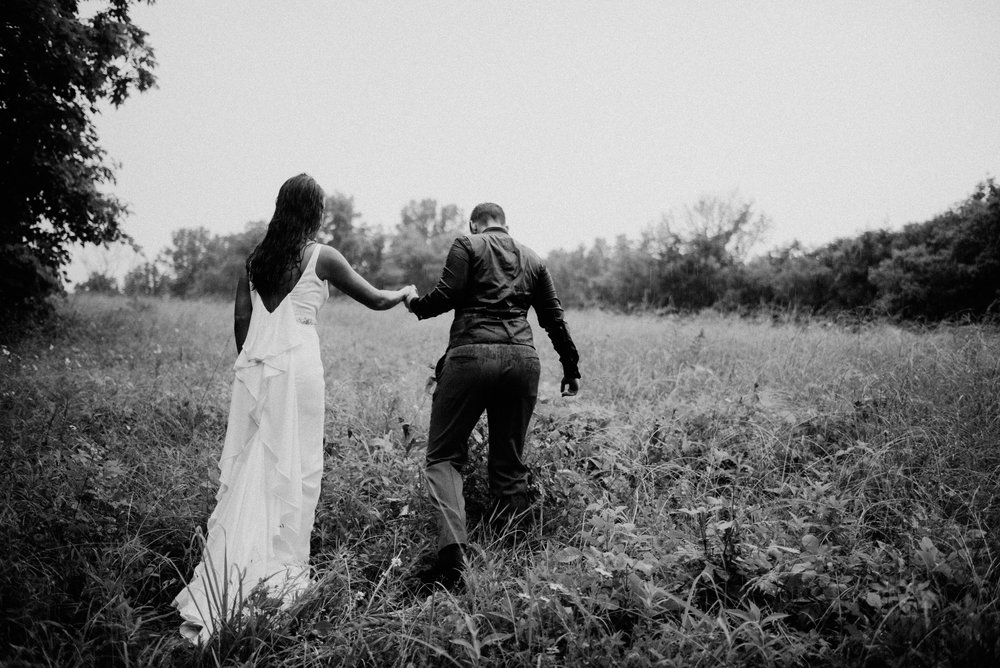 black and white photo of two married women in their wedding attire walking through field in the rain