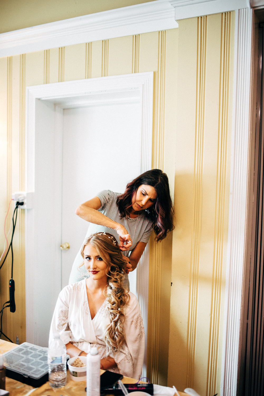bride in a robe getting her hair done by hairstylist before wedding