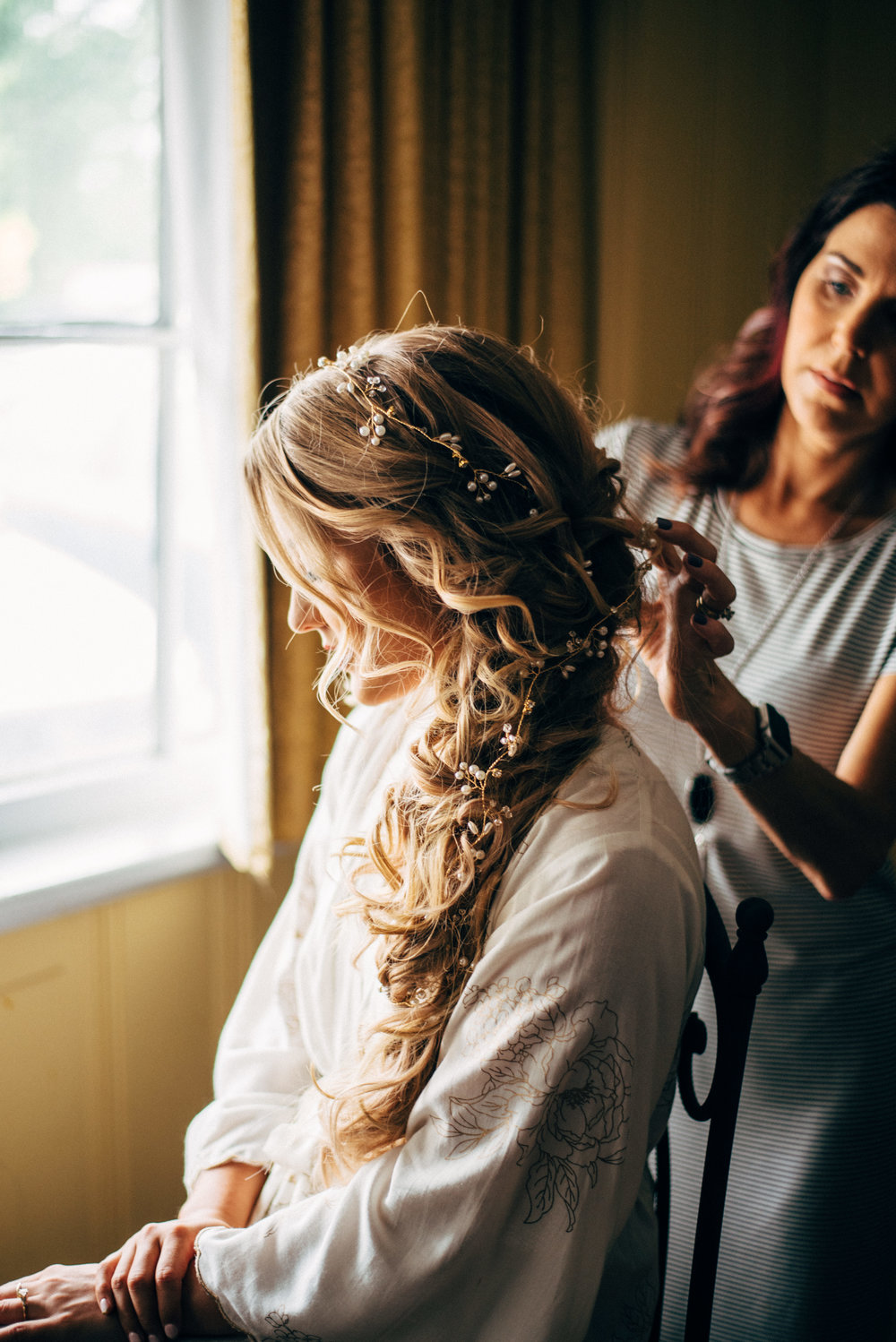 hairdresser putting final touches on bride's mermaid hair before the wedding