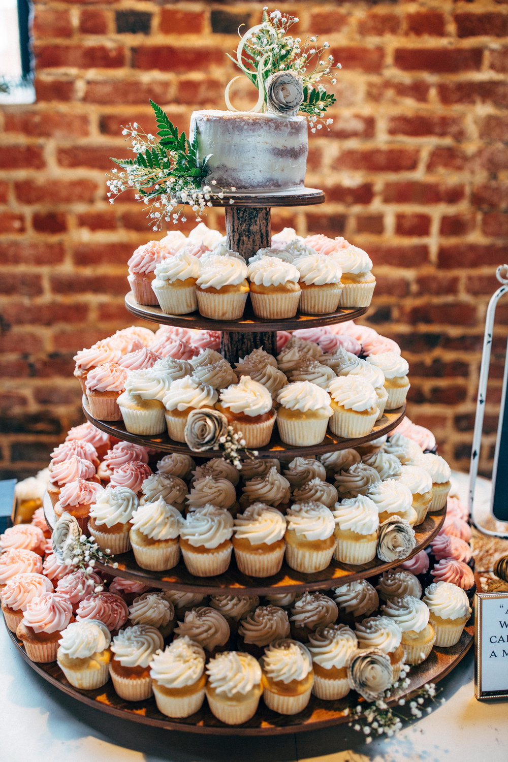 cupcake tower with wedding cake topper at reception