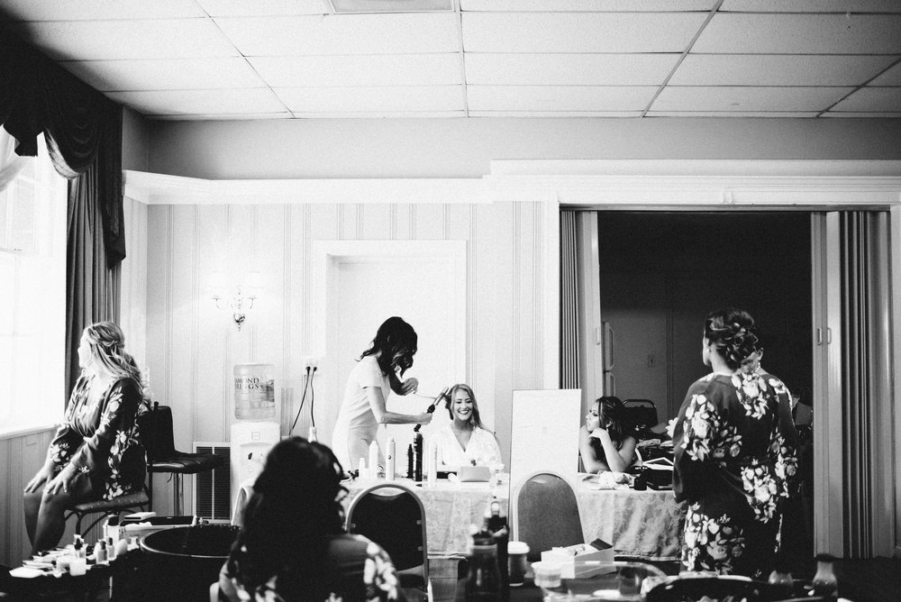 black and white photo of bride smiling while getting her hair curled before wedding