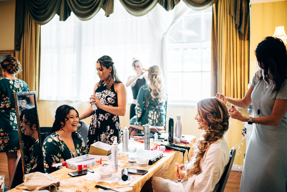bride and bridesmaids getting their hair done before the wedding