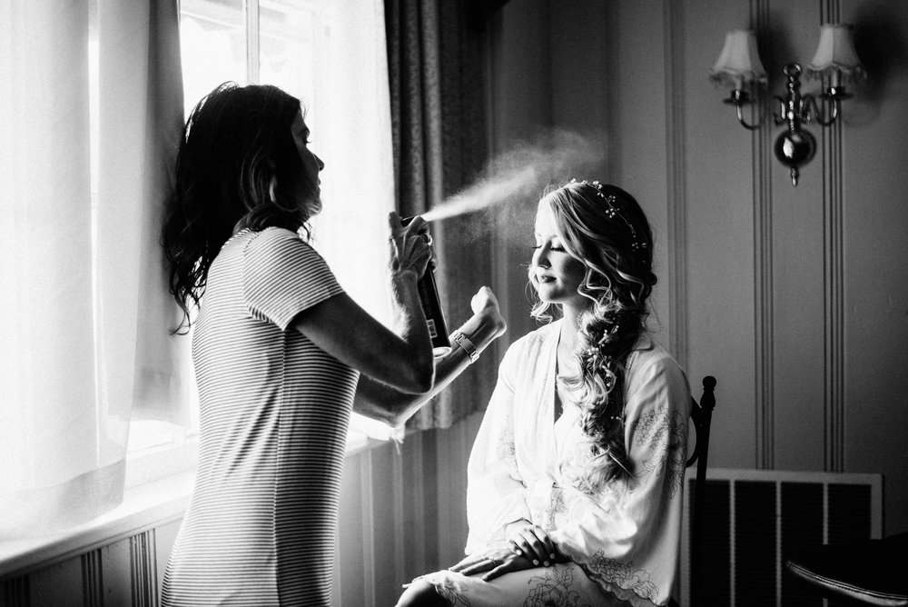 black and white photo of hairdresser using hairspray on bride before wedding