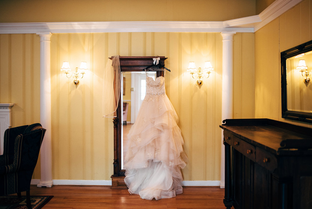 white wedding dress hanging on mirror at The Inn at the Old Silk Mill