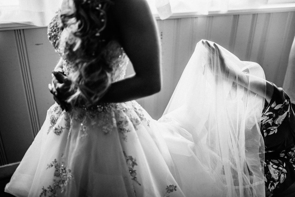 black and white photo of bride in her sequined wedding dress while bridesmaid adjusts dress