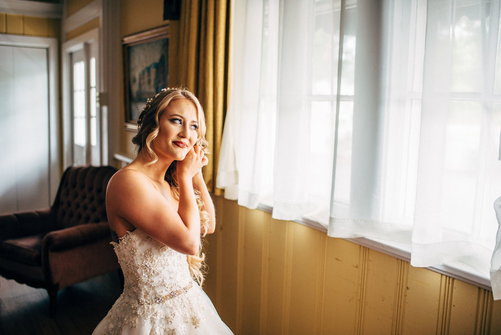 bride in front of a window while putting on her jewelry before wedding ceremony