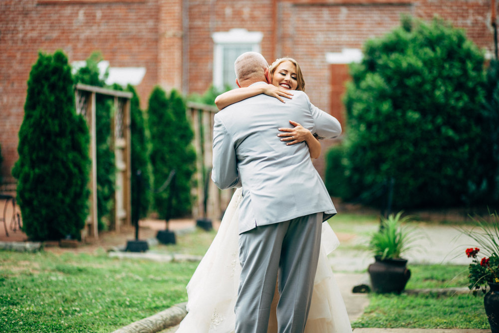 father and daughter hugging on wedding day with brick building in background