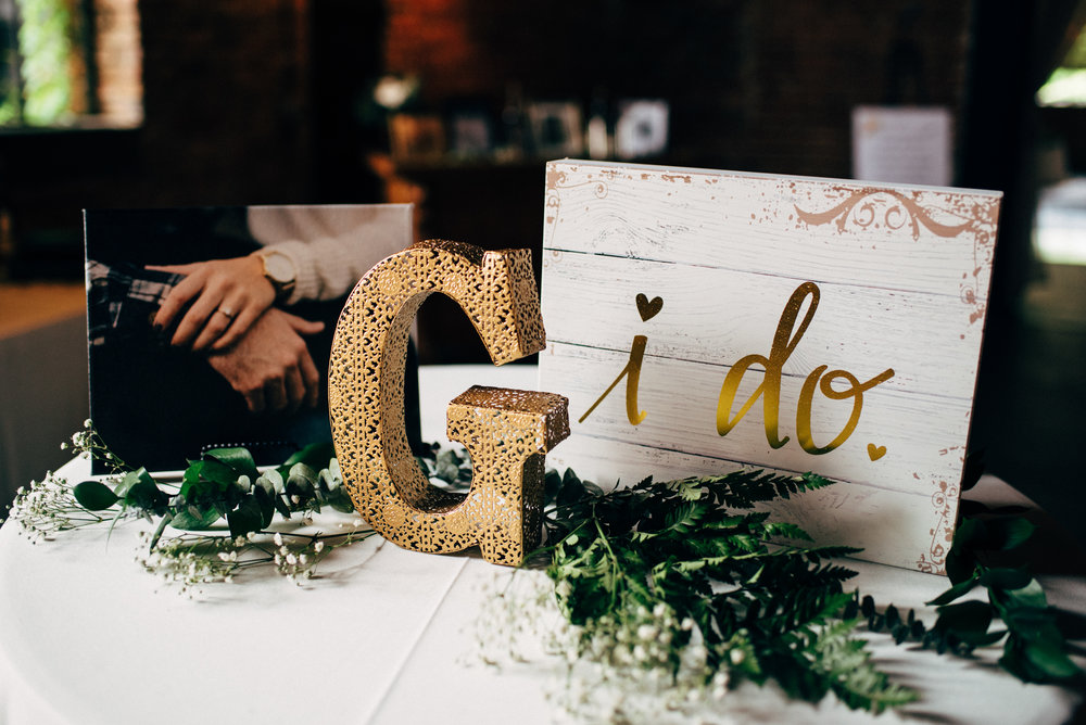 photo of couple's hands and wooden sign at wedding reception at the Inn at the Old Silk Mill