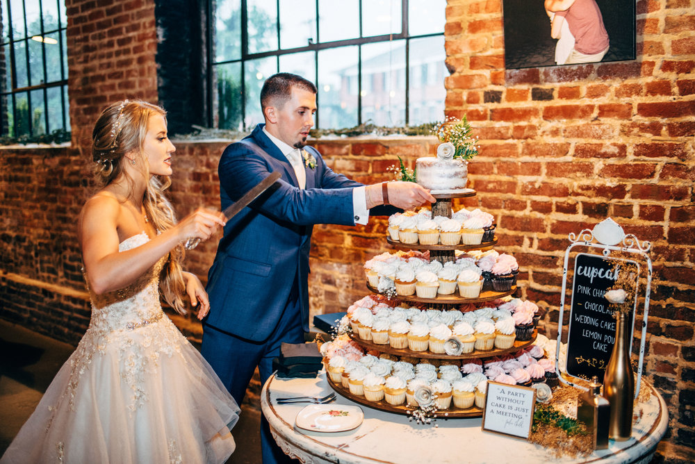 bride holds knife as the groom removes wedding cake from the cupcake tower during wedding reception