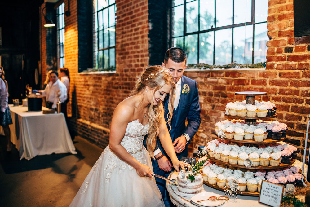 bride and groom cutting the cake during their wedding reception at The Inn at the Old Silk Mill