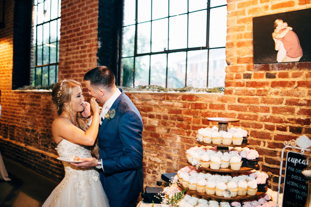 bride and groom feed each other cake during their wedding reception at The Inn at the Old Silk Mill