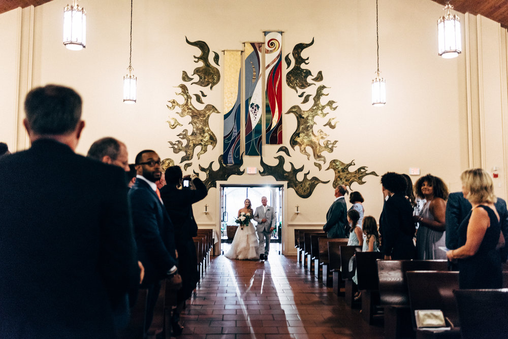the bride and her father entering the the sanctuary at St. Francis of Assisi Catholic Church