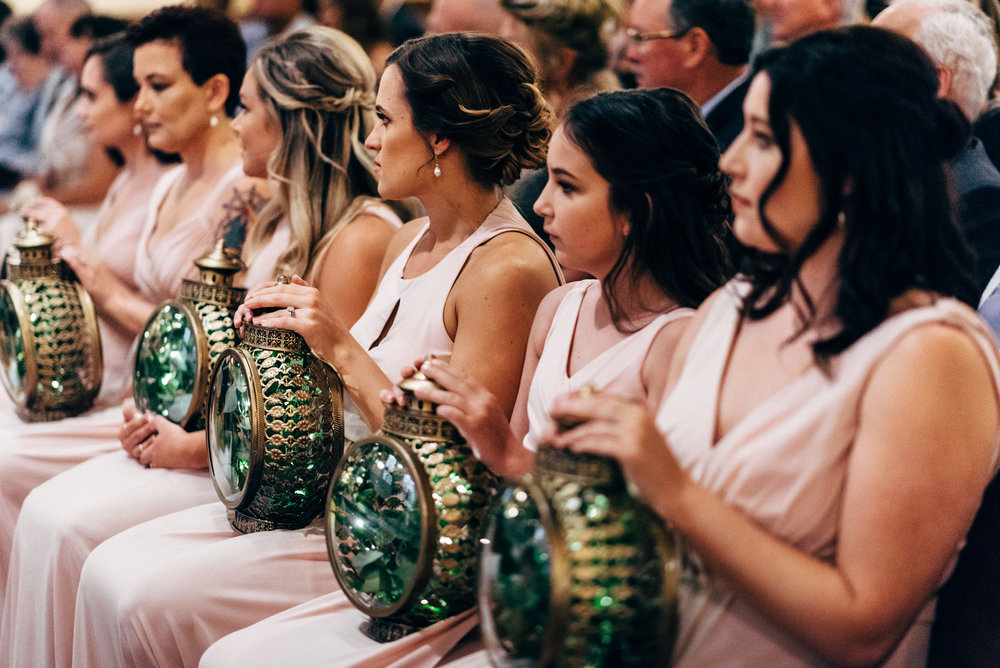 bridesmaids sitting with lanterns during wedding ceremony at St. Francis of Assisi Catholic Church