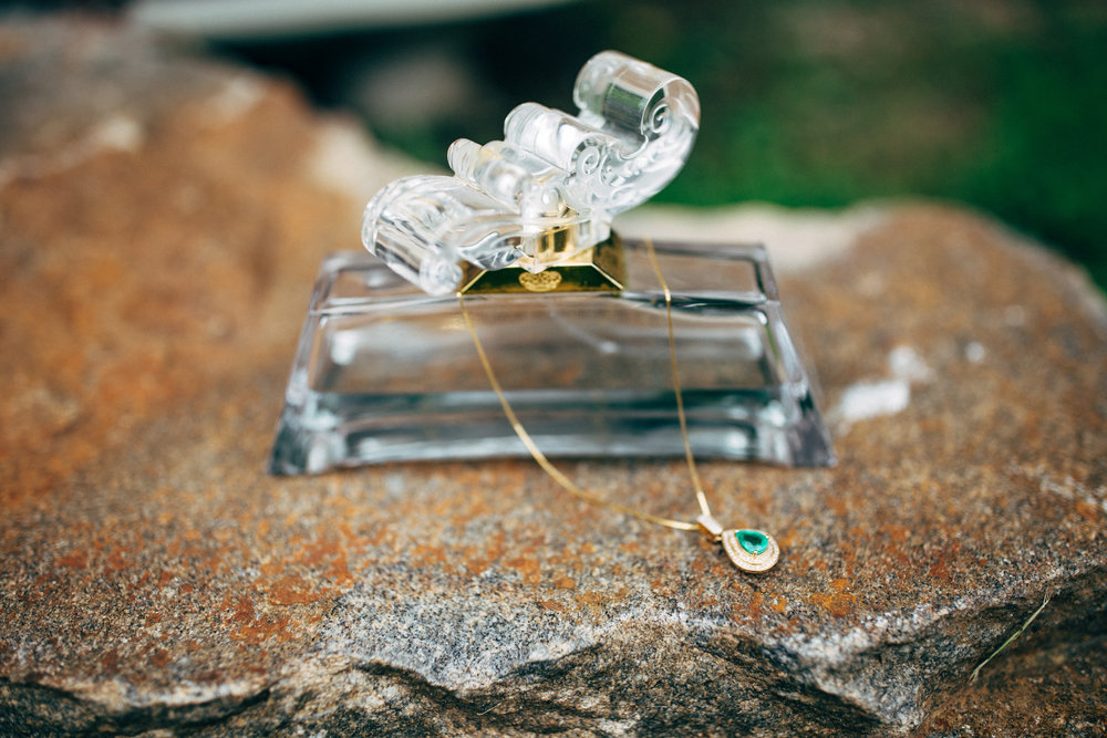 Perfume bottle with gold and emerald necklace