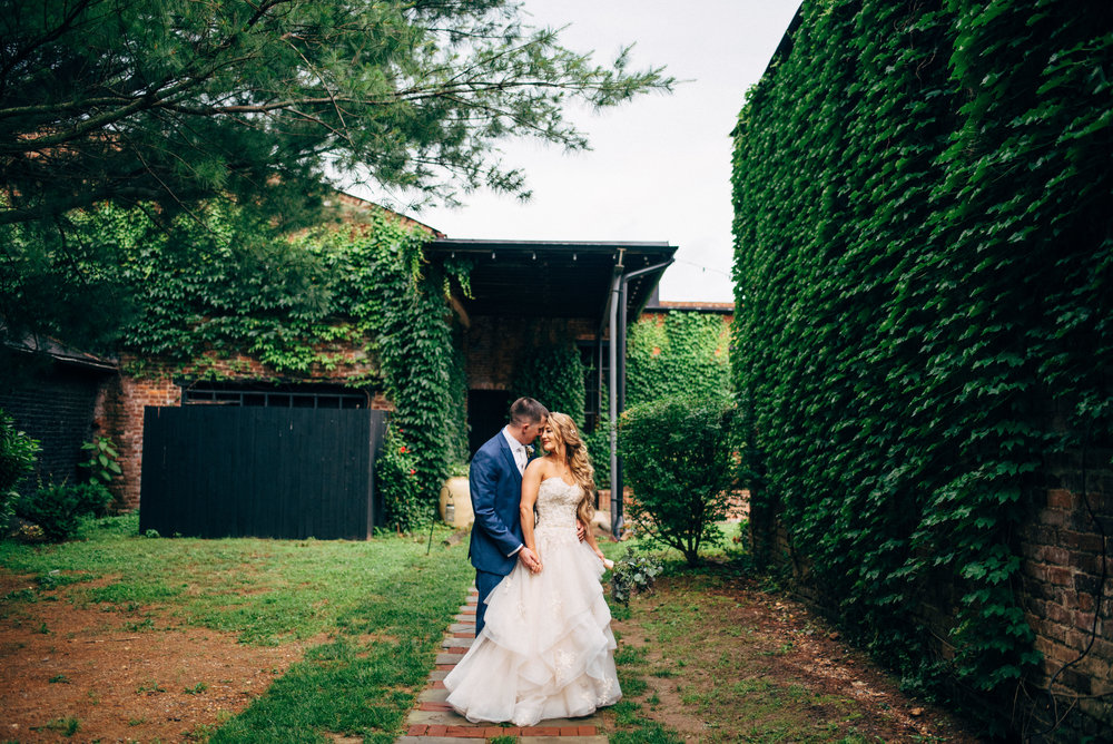 fairy-tale bride and groom on path in front of ivy covered building at The Inn at the Old Silk Mill