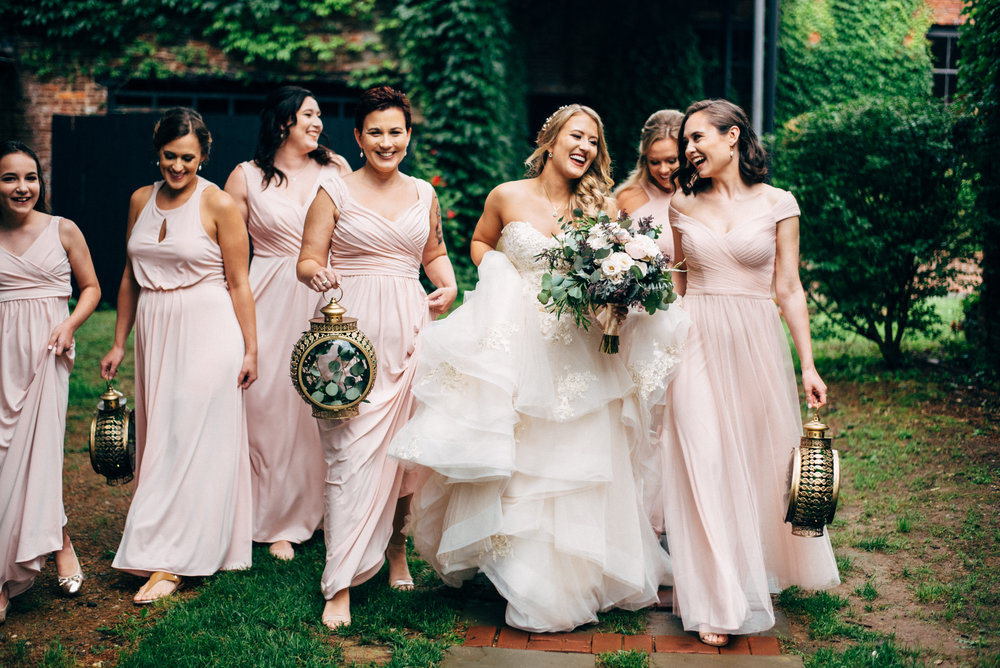 bride laughing with her bridemaids in front of ivy covered wall
