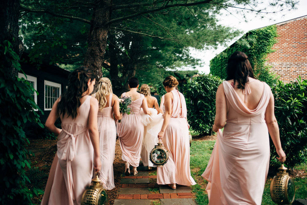 bride walking down path with her bridesmaids behind her dressed in pink and holding lanterns
