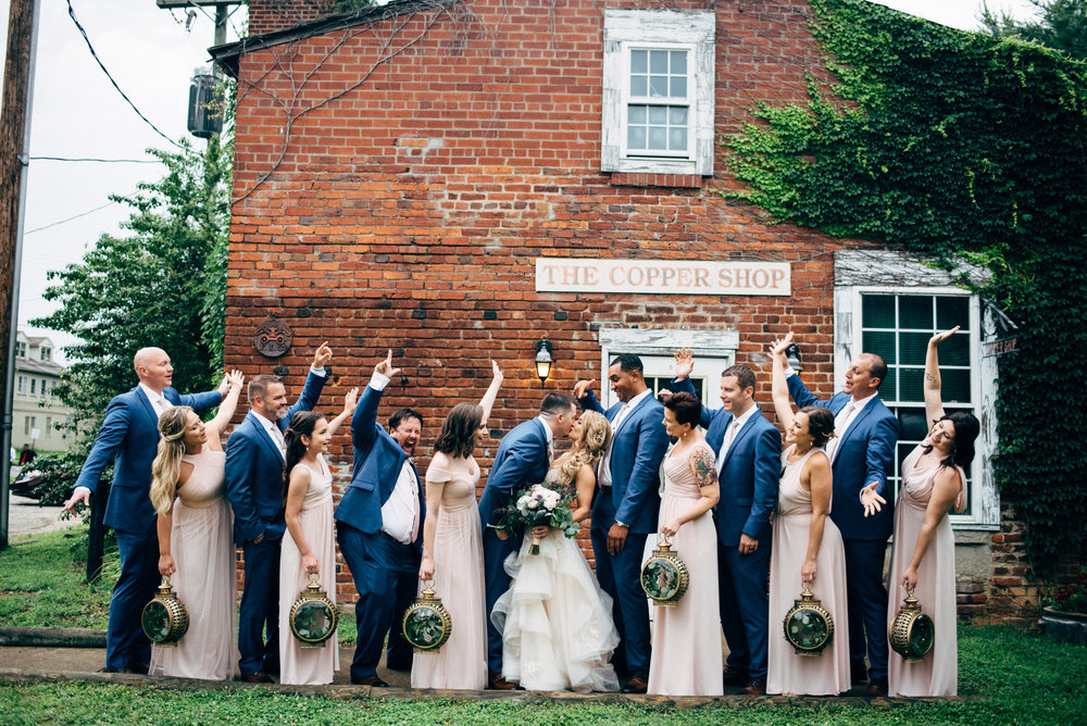 bridal party cheering as bride and groom kiss at the Old Silk Mill in Fredericksburg, VA