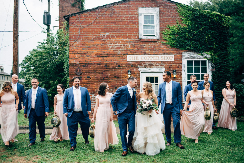 bridal party walking alongside the bride and groom in front of brick building