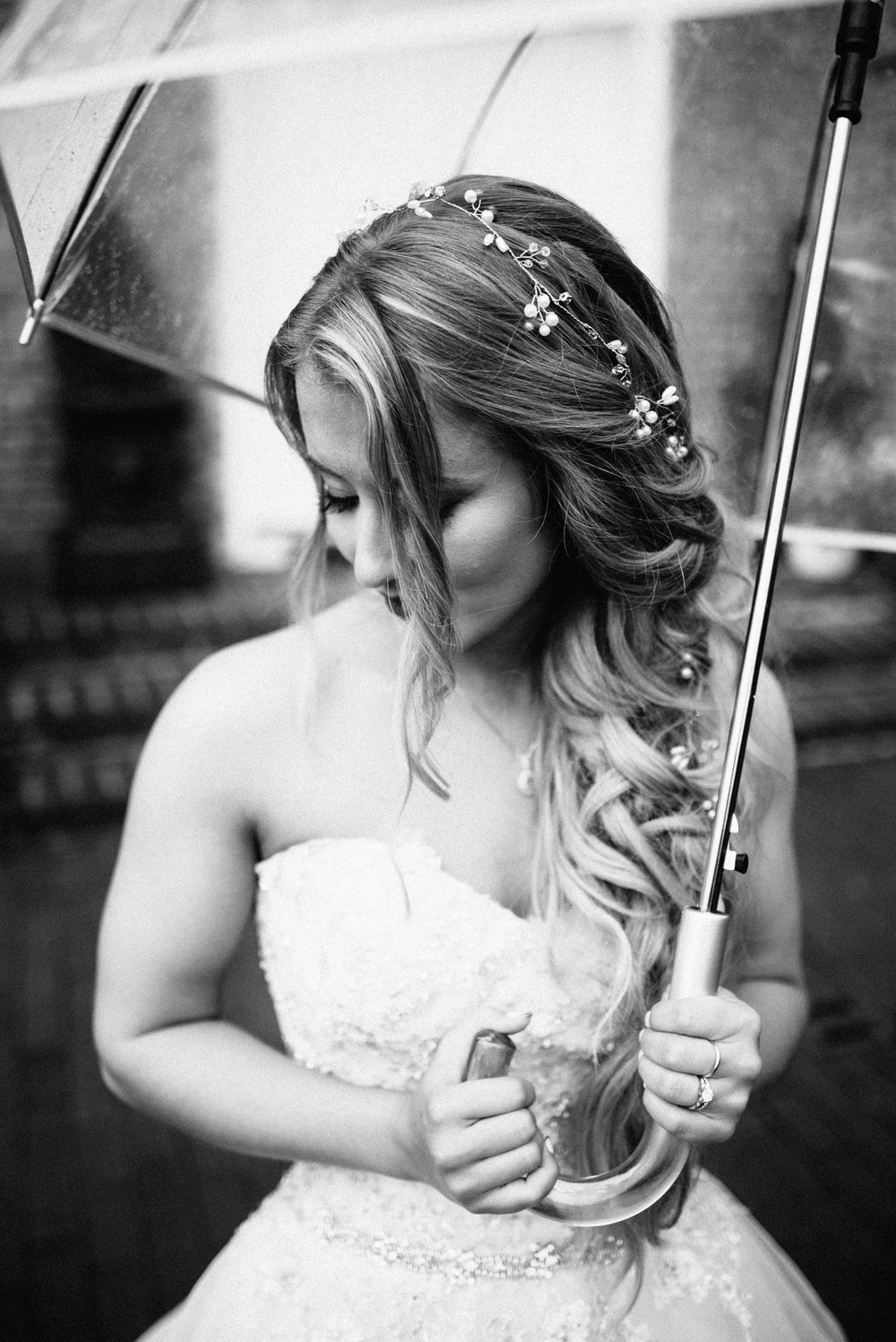 black and photo of bride with mermaid hair in sequined wedding dress holding a clear umbrella