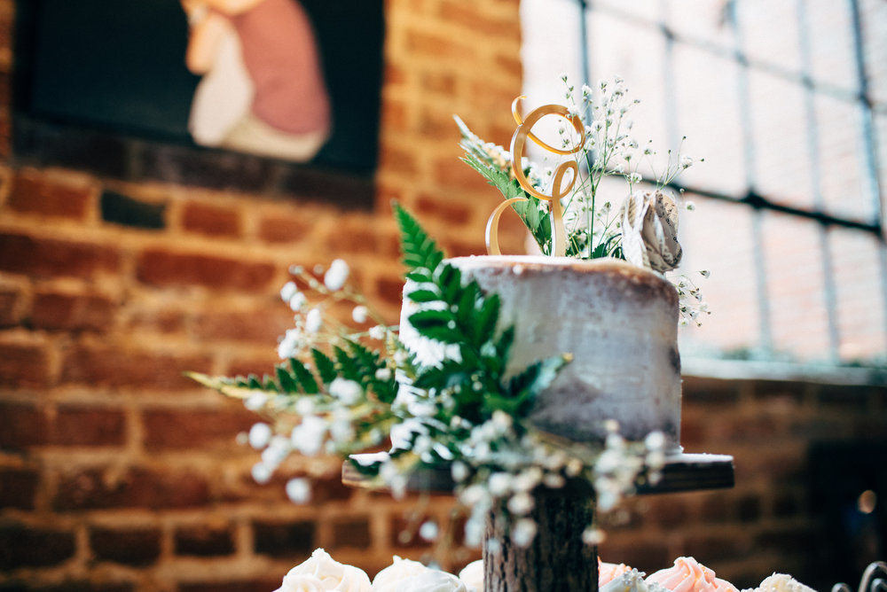 "wedding cake decorated with cursive ""G"" wedding topper, baby's breath, and greenery in front of brick wall"