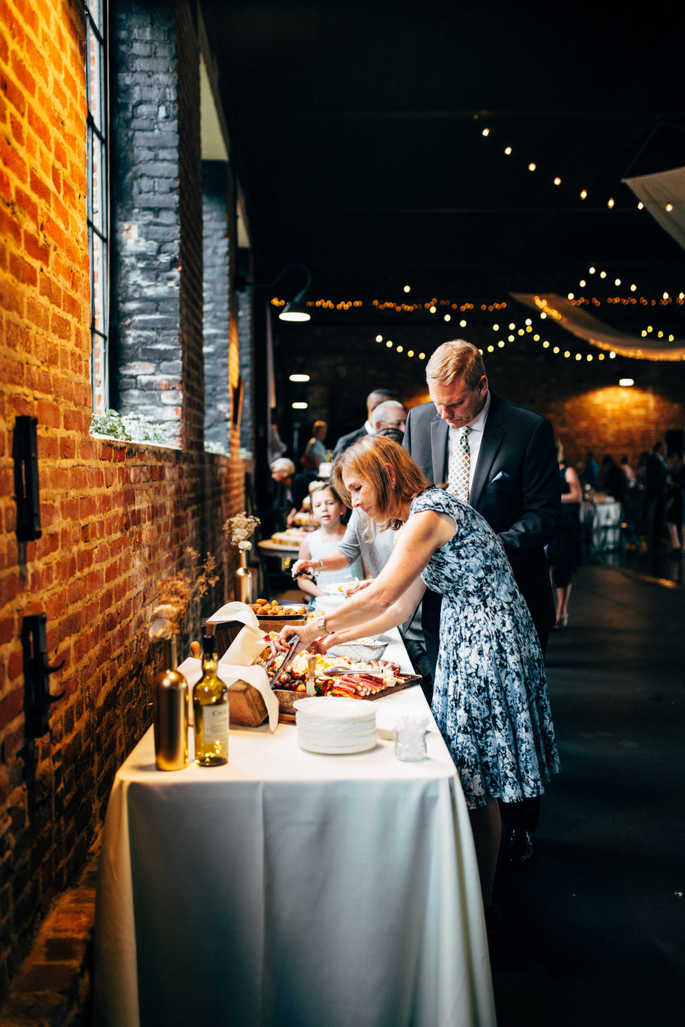 wedding guests eat from charcuterie board during cocktail hour at reception at the Inn at the Old Silk Mill