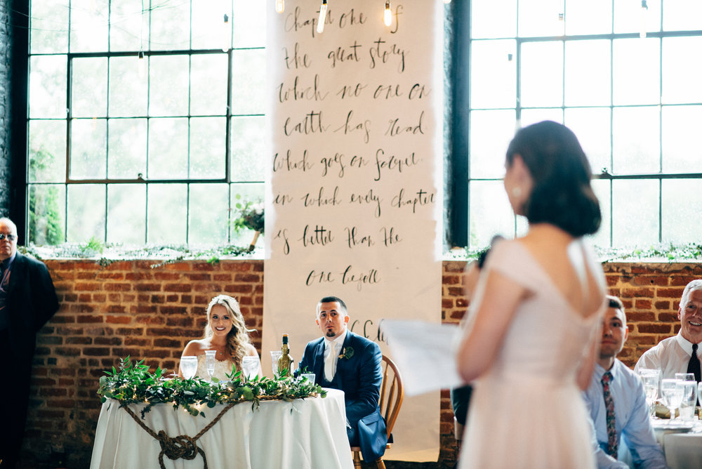bride and groom watch as the maid of honor gives speech during wedding reception at the Inn at the Old Silk Mill