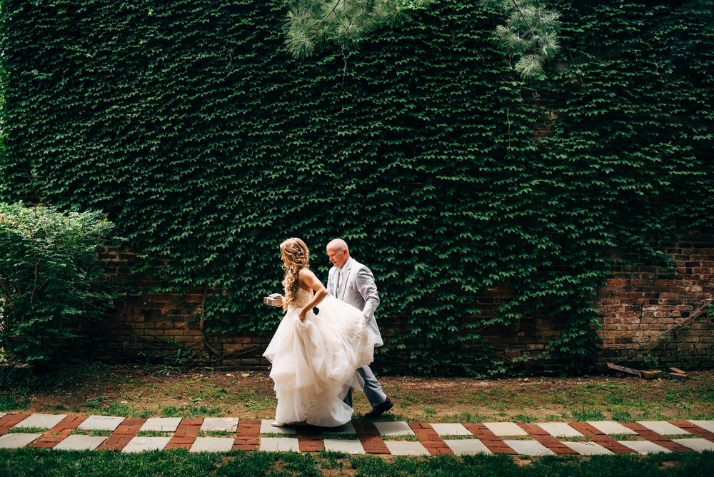 Father of the bride holds his daughter's train while walking down path in front of ivy covered wall