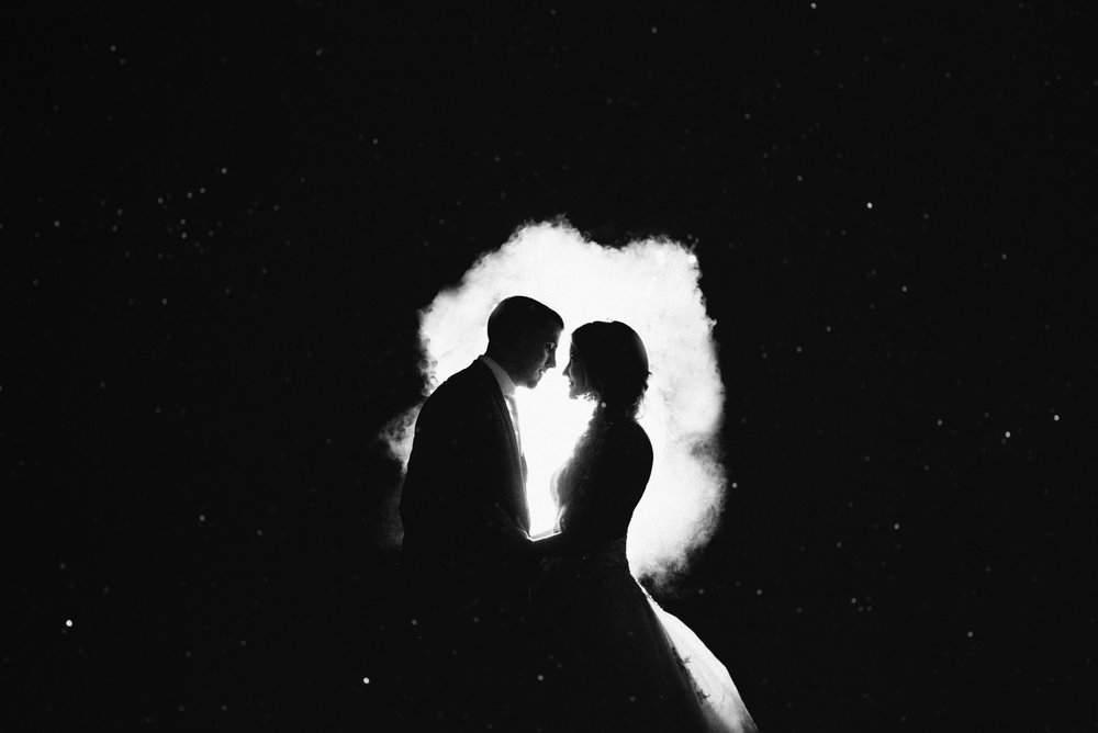 black and white silhouette of fairytale bride and groom at night surrounded by stars