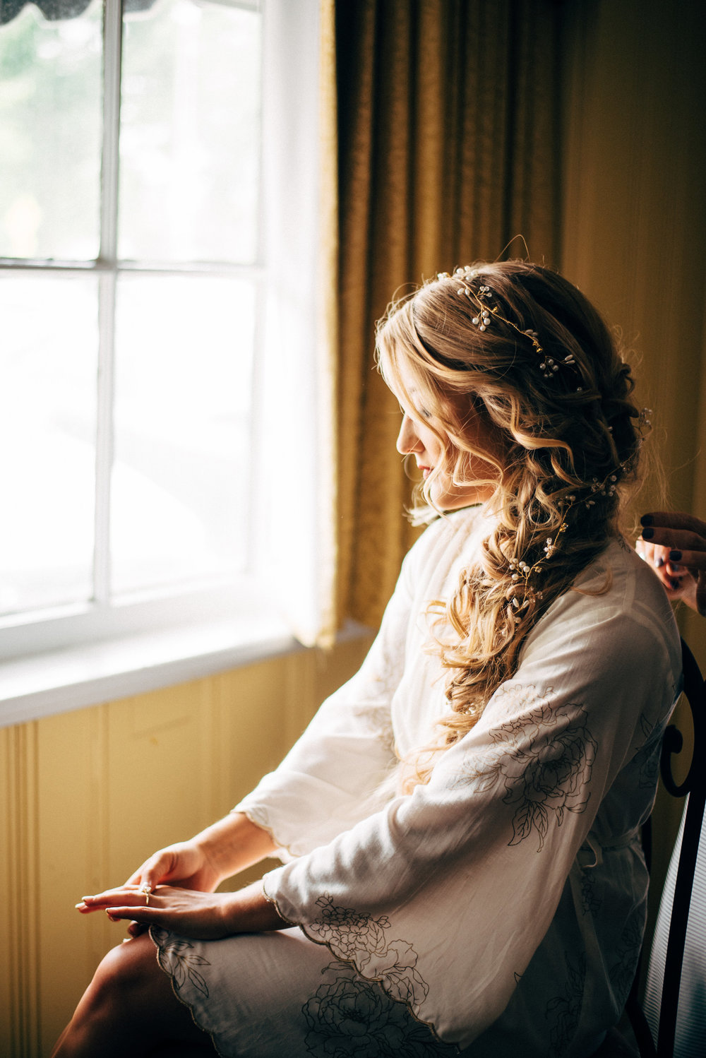 bride with mermaid hair in her robe before the wedding with sunlight on face