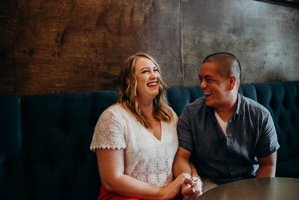 engaged couple laughing together in record store cafe in Washington DC